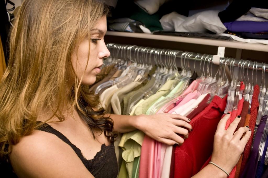 kobieta wybierająca ubrania znajdujące się w szafie przesuwnej
